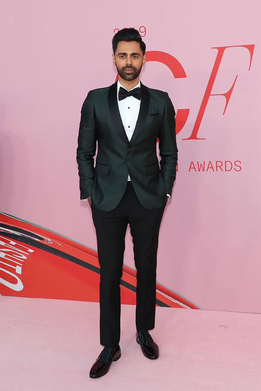 Hasan Minhaj in black pants